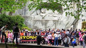 Mass tourists taking a group picture in front of Lion monument, Lucerne Switzerland