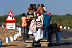 Mass transit in India. Workers in the Rann of Kutch district of Gujarat, India, negotiating space on an overcrowded vehicle that will take them to their Royalty Free Stock Photography