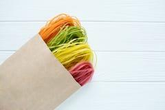Massa colorido cru em um saco de papel Fotos de Stock