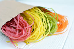 Massa colorido cru em um saco de papel Imagens de Stock