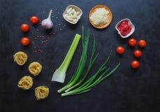 Massa com cogumelos Ingredientes para os espaguetes em um fundo preto Fotografia de Stock