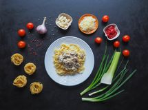 Massa com cogumelos Ingredientes para os espaguetes em um fundo preto Fotografia de Stock Royalty Free