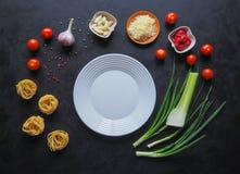 Massa com cogumelos Ingredientes para os espaguetes em um fundo preto Fotos de Stock