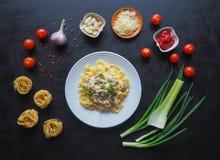 Massa com cogumelos Ingredientes para os espaguetes em um fundo preto Imagens de Stock