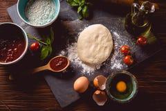 Massa com farinha na tabela de madeira, preparando a pizza caseiro Foto de Stock