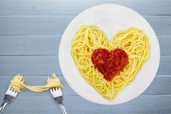 Massa com molho de tomate na forma do coração com dois Fotografia de Stock Royalty Free