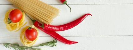 Massa com tomate, pimentas de pimentão, alecrins na tabela branca Imagem de Stock
