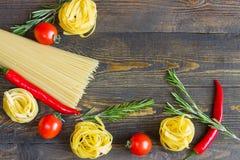 Massa com tomate, pimentas de pimentão, alecrins na tabela de madeira Vista superior fotos de stock