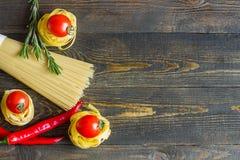 Massa com tomate, pimentas de pimentão, alecrins na tabela de madeira Vista superior imagens de stock royalty free