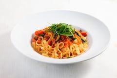 Massa com vegetais, tomates, abobrinha, pimentas, isoladas no menu redondo branco da placa do molho de tomate do fundo Imagem de Stock Royalty Free