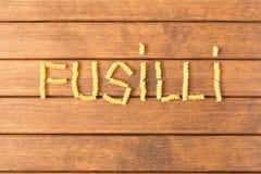 Massa cru do fusilli Em uma tabela de madeira Alimento italiano fotografia de stock