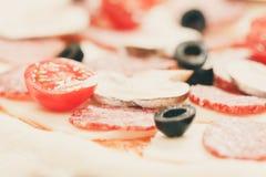 Massa crua da pizza com azeitona sobre o cozimento da mussarela, do tomate e do salame fotografia de stock