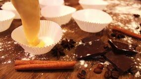 A massa crua para queques no prato do cozimento do papel especial polvilhado com o chocolate remenda vídeos de arquivo