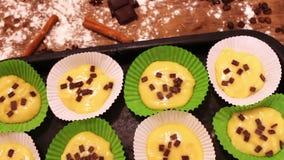 A massa crua para queques no prato do cozimento do papel especial polvilhado com o chocolate remenda filme