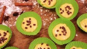 A massa crua para queques no prato do cozimento do papel especial polvilhado com o chocolate remenda video estoque