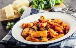 Massa Culinária do italiano e do Mediterrannean A massa Rigatoni com manjericão do molho de tomate sae do alho e do queijo parmes Foto de Stock Royalty Free