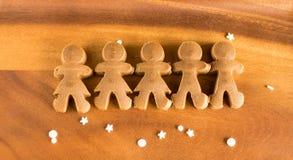 Massa das meninas e dos meninos do pão-de-espécie no fundo de madeira Imagem de Stock