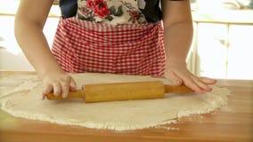 Massa de amasso do padeiro com o pino do rolo na tabela Massa do rolamento da mulher para a pizza Massa do rolamento para a pizza video estoque