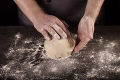 Massa de amasso do padeiro das mãos no desktop, no preto imagem de stock royalty free