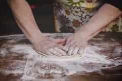 Massa de amasso do padeiro fêmea idoso na tabela de madeira Imagem de Stock