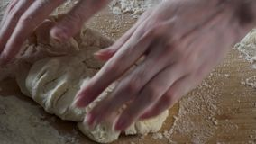 Massa de amasso do padeiro na farinha na tabela cena O cozinheiro chefe do homem amassa a massa As mãos amassam a massa em uma ta vídeos de arquivo
