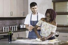 Massa de amasso dos pares felizes da raça misturada junto na cozinha Imagem de Stock