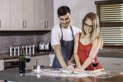 Massa de amasso dos pares felizes junto na cozinha Fotos de Stock