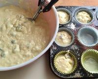 Massa de escavação do muffin de blueberry em copos para cozer Imagem de Stock Royalty Free