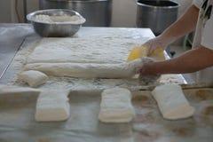 Massa de pão de Cutting Raw Ciabatta do padeiro fotos de stock royalty free