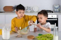 Massa do cozinheiro de dois meninos para bolos na cozinha imagens de stock royalty free