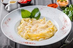 Massa do Fettuccine com queijo parmesão, manjericão e molho de creme no fundo de madeira escuro imagem de stock