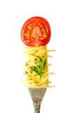 A massa dos espaguetes com manjericão e um ramo das hortaliças ferem-se em uma forquilha com uma parte de tomates de cereja isola Imagem de Stock Royalty Free