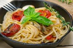 Massa dos espaguetes com os tomates e manjericão cozidos de cereja Fotografia de Stock