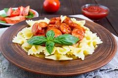 Massa em uma bacia cerâmica, saque de Farfalle com ketchup, tomates frescos, salsicha no molho de tomate Fotos de Stock