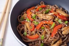 Massa escura com vegetais cozinhados e a galinha grelhada Macarronetes deliciosos do trigo mourisco com vegetais e galinha imagem de stock