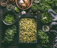 Massa fresca verde com o pesto da couve, cozinhando a preparação na tabela escura com ingredientes e utensílios da cozinha Refeiç fotografia de stock royalty free