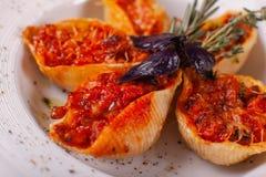 Massa italiana Conchiglioni Rigati Prato delicioso enchido com carne à terra com os tomates secos no molho de tomate Close up sob imagem de stock royalty free