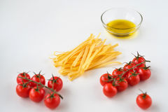 Massa italiana cru, azeite e cereja dos tomates em um branco Imagem de Stock