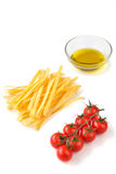 Massa italiana cru, azeite e cereja dos tomates em um branco Fotografia de Stock