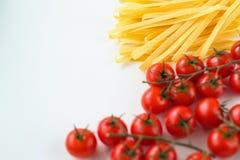 Massa italiana cru e cereja dos tomates em um fundo branco Fotos de Stock