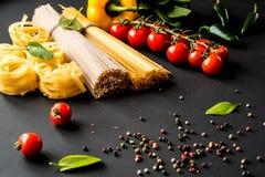 Massa italiana crua Espaguetes e fettuccine com tomates, vegetais, ervas e pimenta em um fundo preto closeup fotos de stock