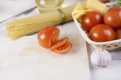 Massa italiana que cozinha ainda a vida Espaguetes ou macarrão seco, óleo do oliv, tomates, verde e queijo na mesa de cozinha de  Fotos de Stock