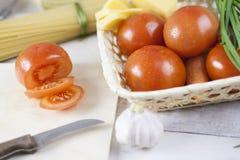 Massa italiana que cozinha ainda a vida Espaguetes ou macarrão seco, óleo do oliv, tomates, verde e queijo na mesa de cozinha de  Foto de Stock Royalty Free