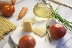 Massa italiana que cozinha ainda a vida Espaguetes ou macarrão seco, óleo do oliv, tomates, verde e queijo na mesa de cozinha de  Fotos de Stock Royalty Free