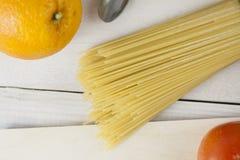 Massa italiana que cozinha ainda a vida Espaguetes ou macarrão seco, óleo do oliv, tomates, verde e queijo na mesa de cozinha de  Foto de Stock