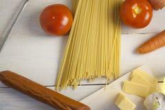 Massa italiana que cozinha ainda a vida Espaguetes ou macarrão seco, óleo do oliv, tomates, verde e queijo na mesa de cozinha de  Fotografia de Stock Royalty Free