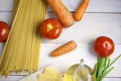 Massa italiana que cozinha ainda a vida Espaguetes ou macarrão seco, óleo do oliv, tomates, verde e queijo na mesa de cozinha de  Imagens de Stock