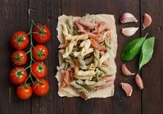 Massa, manjericão, tomates e alho inteiros do trigo Fotografia de Stock Royalty Free
