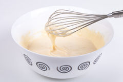Massa misturada em uma bacia e em um batedor de ovos Fotografia de Stock