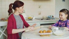 Massa nova do rolamento da mãe e fala à filha bonito pequena ao cozinhar na cozinha no fim de semana Família, alimento vídeos de arquivo